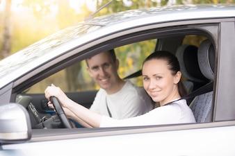 Jovem mulher dirigindo, um homem sentado perto do carro