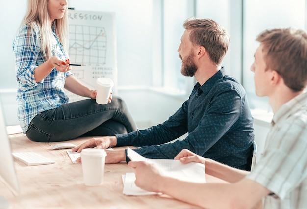 Jovem mulher discutindo com os colegas a nova estratégia. o conceito de trabalho em equipe