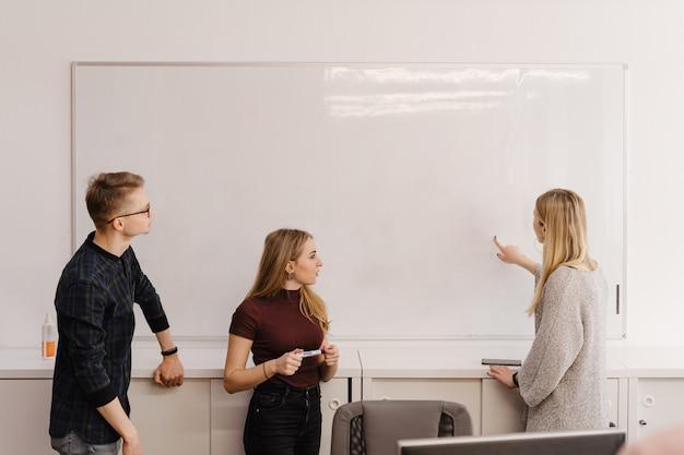 Jovem mulher discutindo com os colegas sobre o quadro branco no escritório
