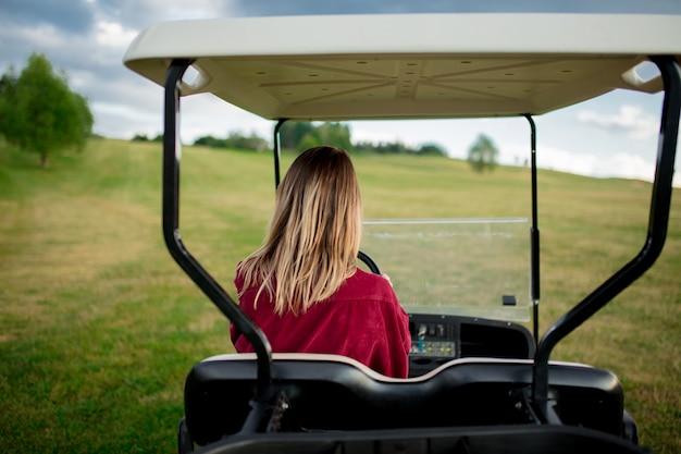 Jovem, mulher, divirta-se com o carro de buggy de golfe em um campo nas montanhas