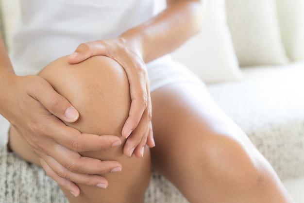 Jovem mulher do close up que senta-se no sofá e que sente a dor do joelho.