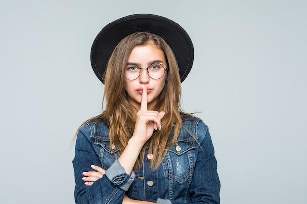 Jovem mulher do retrato que mostra o gesto do silêncio sobre o fundo cinzento