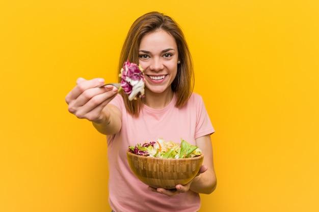 Jovem mulher do vegetariano que come uma salada fresca e deliciosa.