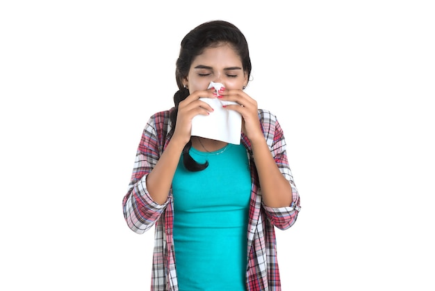 Jovem mulher doente assoando o nariz. rinite alérgica. está com febre. jovem com frio