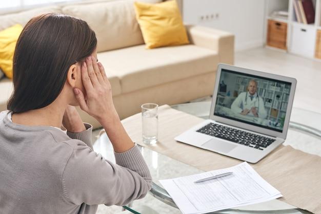 Jovem mulher doente com as mãos nas têmporas, sentada à mesa em frente ao latop durante consulta médica online