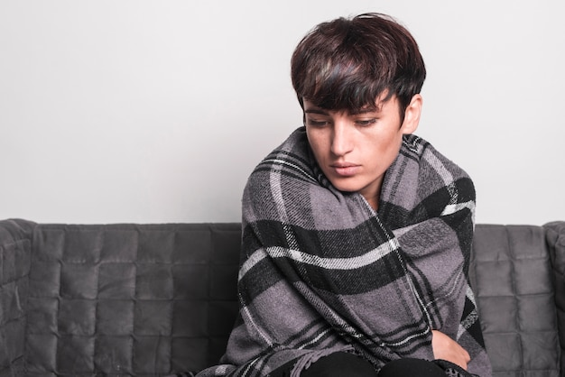 Jovem mulher doente embrulhado no cobertor sentado no sofá