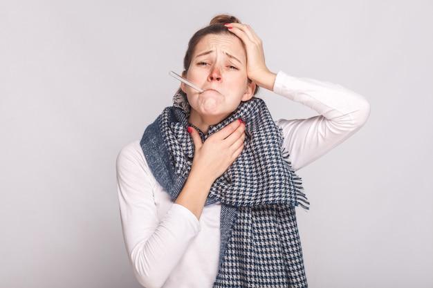 Jovem mulher doente segurando a garganta e a cabeça. tem uma temperatura. foto de estúdio, isolada em fundo cinza