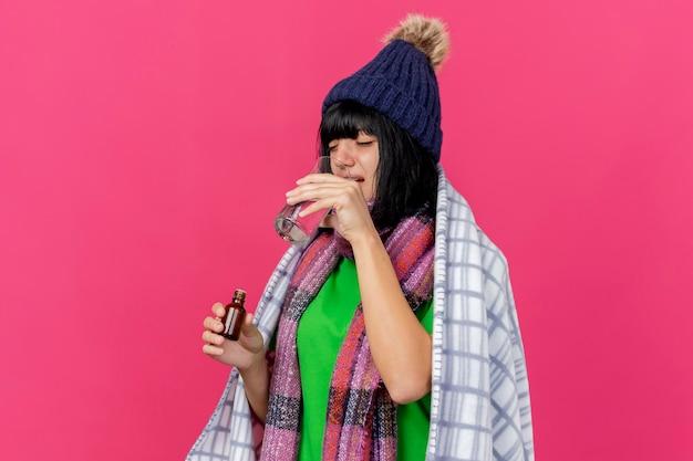 Jovem mulher doente usando chapéu de inverno e lenço embrulhado em manta segurando medicamento em um copo de vidro bebendo água isolado na parede rosa com espaço de cópia