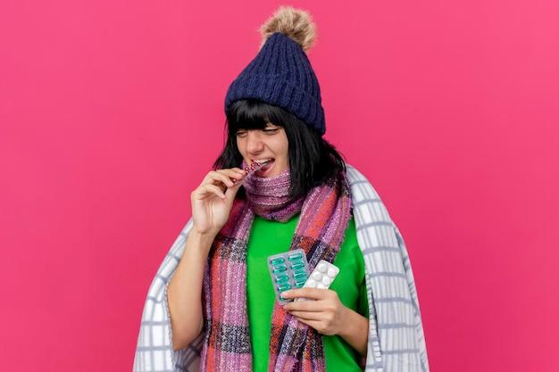 Jovem mulher doente usando chapéu de inverno e lenço embrulhado em manta segurando pacotes de comprimidos médicos e mordendo um deles, olhando para o lado isolado na parede rosa com espaço de cópia