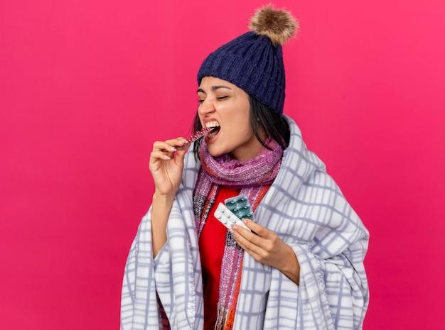 Jovem mulher doente usando chapéu de inverno e lenço embrulhado em manta segurando pacotes de pílulas, mordendo um deles com os olhos fechados, isolado na parede rosa com espaço de cópia