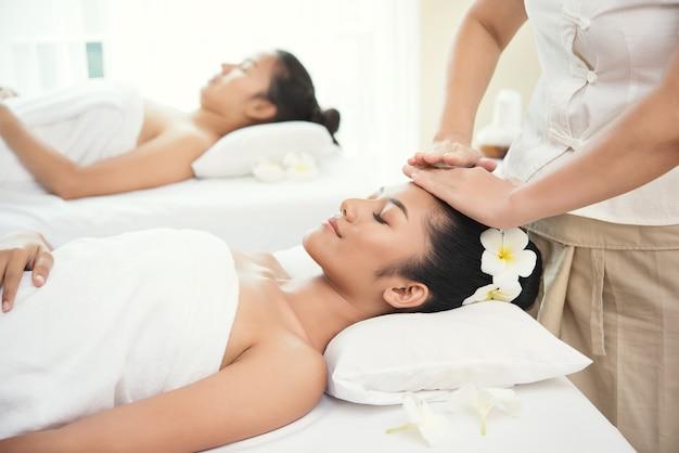 Jovem mulher dois bonita que começ o salão de beleza da massagem dos termas e a flor branca em sua orelha.