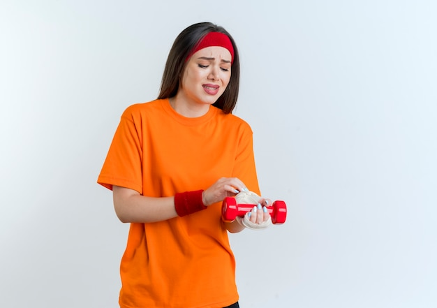 Jovem mulher dolorida e esportiva usando bandagem e pulseiras segurando halteres, tocando e olhando para o pulso ferido envolto em bandagem isolada