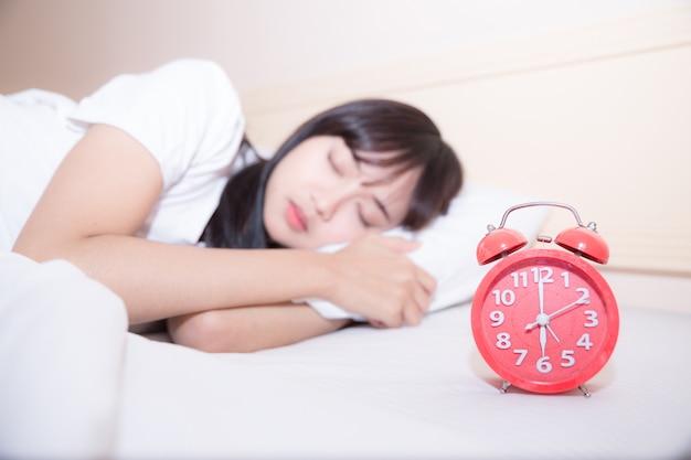 Jovem mulher dormindo e despertador no quarto em casa