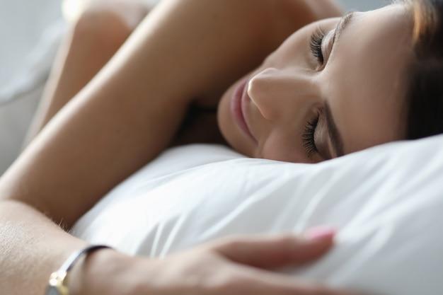 Jovem mulher dormindo pacificamente na roupa de cama branca