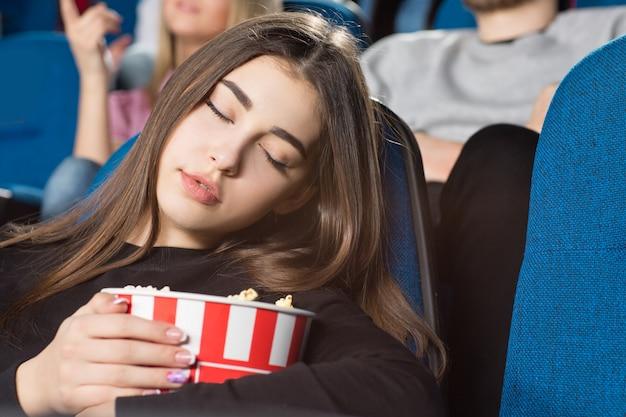 Jovem mulher dormindo segurando seu balde de pipoca no cinema