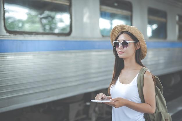 Jovem mulher dos viajantes com a trouxa que olha a tabuleta da posse no estação de caminhos-de-ferro. dia do turismo