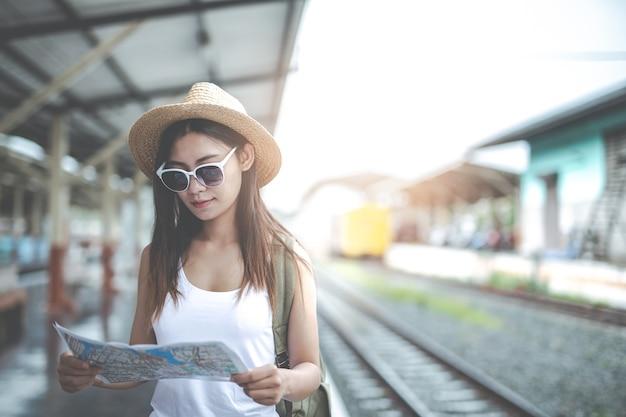 Jovem mulher dos viajantes com a trouxa que olha guarda um mapa na estação de trem. dia do turismo.