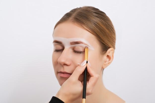 Jovem mulher durante um procedimento de correção de sobrancelha.