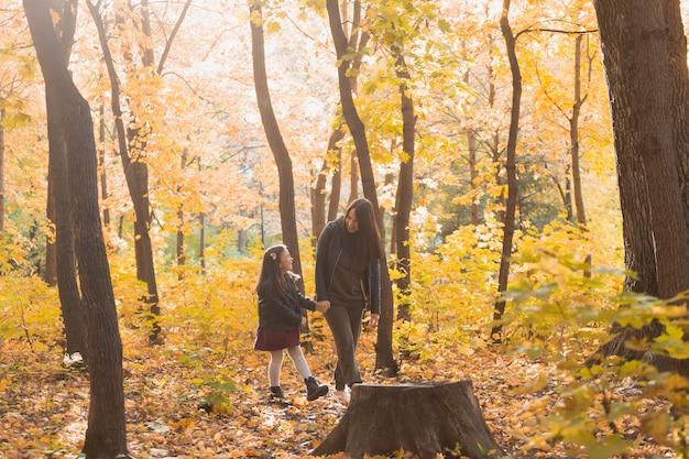 Jovem mulher e a filha dela caminhando pelo parque outono. conceito de mãe solteira e maternidade.