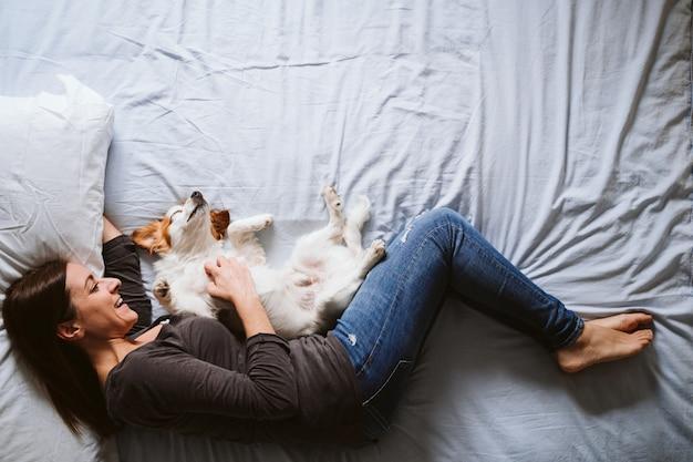 Jovem mulher e cão em casa descansando na cama.