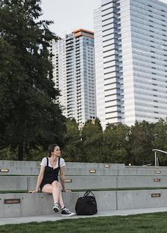 Jovem mulher e edifícios no fundo