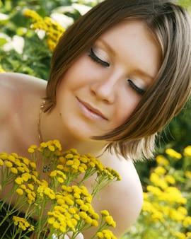 Jovem mulher e flores silvestres.