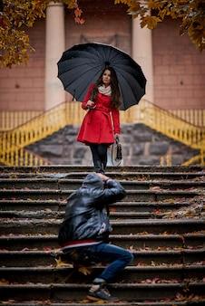 Jovem mulher e fotógrafo no parque na chuva.