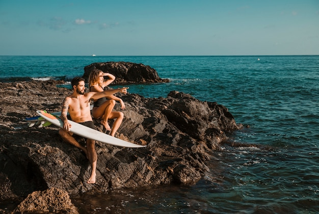 Jovem mulher e homem apontando para o lado com pranchas de surf na rocha perto do mar
