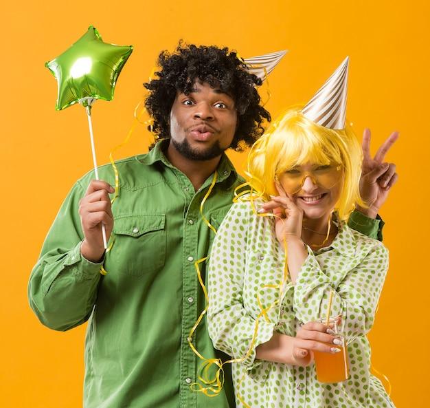 Jovem mulher e homem com balão de festa