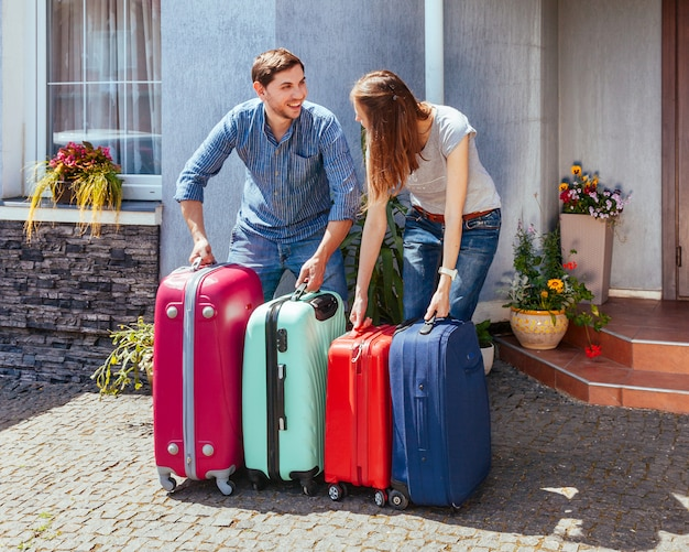 Jovem mulher e homem com muita mala perto de casa pronta para viajar