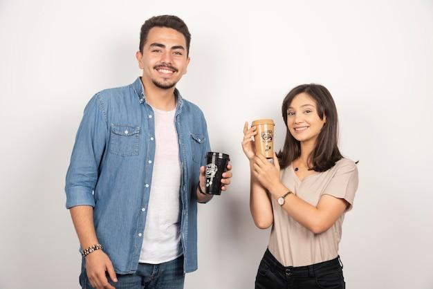 Jovem mulher e homem compartilhando café em branco.
