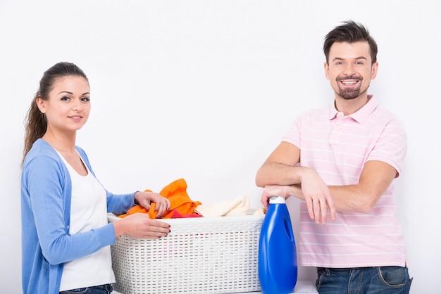 Jovem mulher e homem estão lavando roupa.