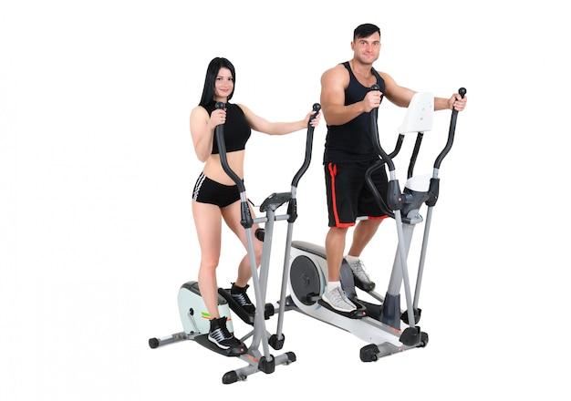 Jovem mulher e homem fazendo exercícios no elíptico cross trainer