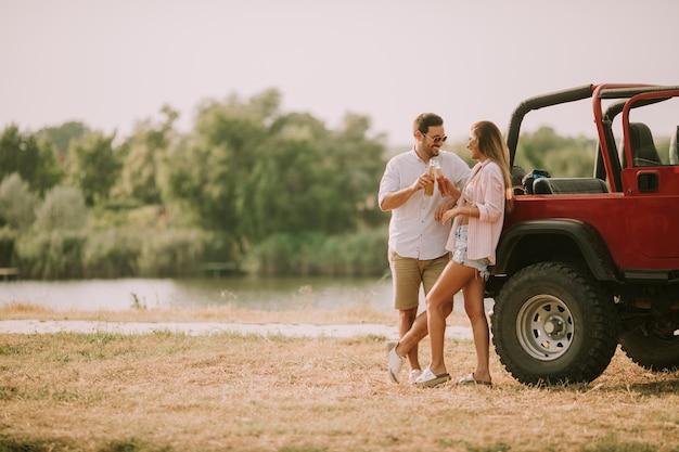 Jovem mulher e homem se divertindo ao ar livre perto de carro