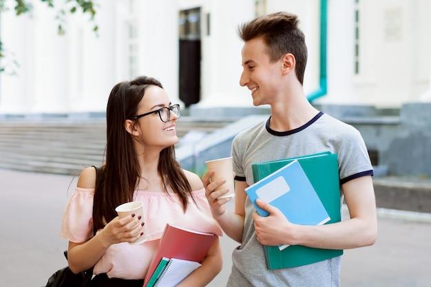 Jovem mulher e homem se divertindo juntos depois das aulas, bebendo café