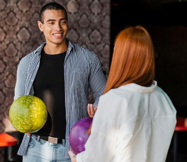Jovem mulher e homem segurando bolas de boliche coloridas tiro médio