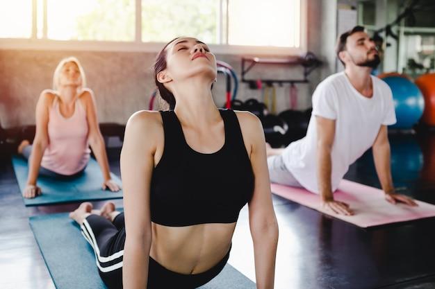 Jovem, mulher, e, men, treinamento, estilo vida, saudável, corporal, malhação, em, ginásio, esportes, estilo, ioga, conceito