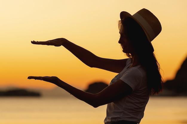 Jovem mulher e pôr do sol no fundo