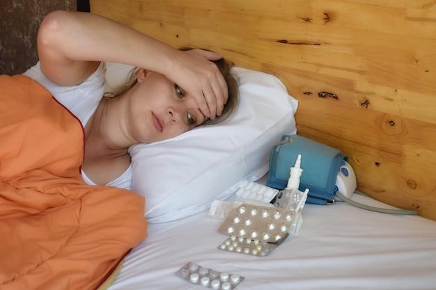 Jovem mulher e remédio na cama