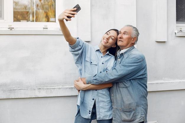 Jovem mulher e seu avô tomando uma selfie