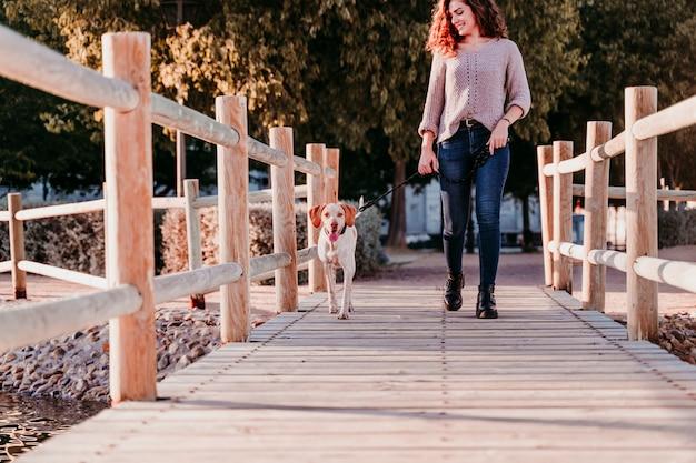 Jovem mulher e seu cachorro andando ao ar livre por uma ponte de madeira em um parque com um lago. dia ensolarado, estação do outono