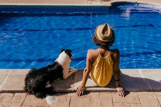 Jovem mulher e seu cachorro border collie na piscina