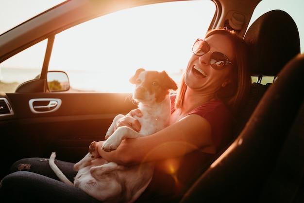 Jovem mulher e seu cachorro fofo em um carro ao pôr do sol. conceito de viagens