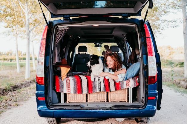 Jovem mulher e seu cão border collie bonito relaxante em uma van. conceito de viagens.