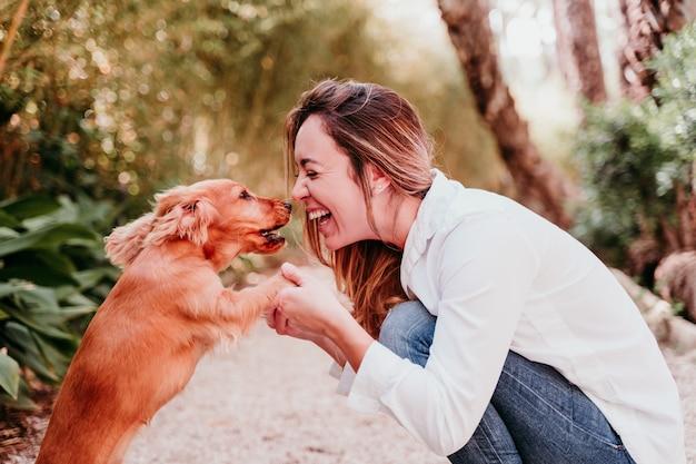 Jovem mulher e seu filhote de cachorro bonito de cocker spaniel ao ar livre em um parque
