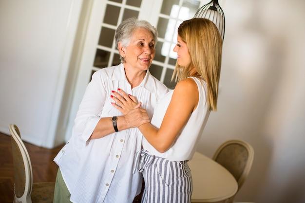 Jovem mulher e sua avó em pé na sala