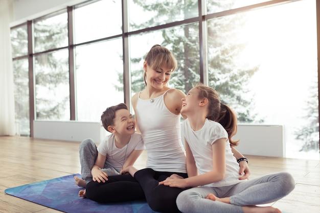 Jovem mulher e sua filha fazendo yoga juntos em casa