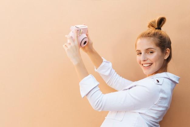 Jovem mulher elegante alegre que toma o selfie na câmera instantânea cor-de-rosa contra o fundo marrom