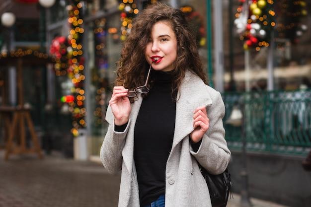 Jovem mulher elegante andando na rua com casaco cinza outono, cabelo encaracolado, frio, tendência da moda estilo casual