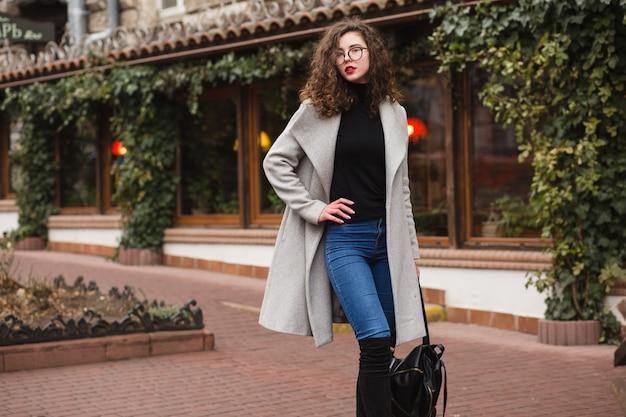 Jovem mulher elegante andando na rua com casaco cinza outono, cabelo encaracolado, frio, usando óculos, tendência da moda estilo casual